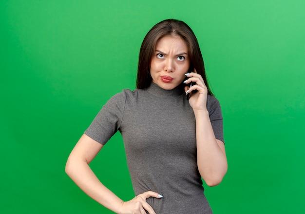 Unzufriedene junge hübsche frau, die am telefon spricht, die hand auf taille setzt und lokalisiert auf grünem hintergrund mit kopienraum nach oben schaut