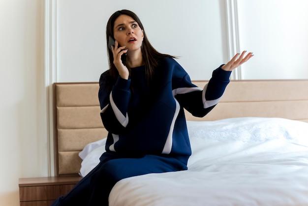 Unzufriedene junge hübsche kaukasische frau, die auf bett im schlafzimmer sitzt und am telefon spricht und seite betrachtet, die leere hand zeigt