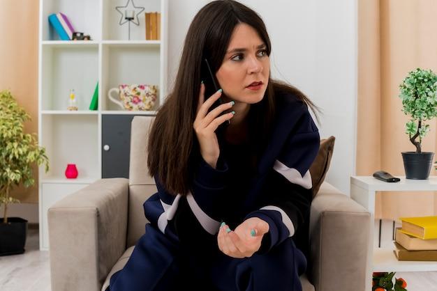 Unzufriedene junge hübsche kaukasische frau, die auf sessel in entworfenem wohnzimmer sitzt und seite betrachtet, die am telefon spricht und hand in luft hält