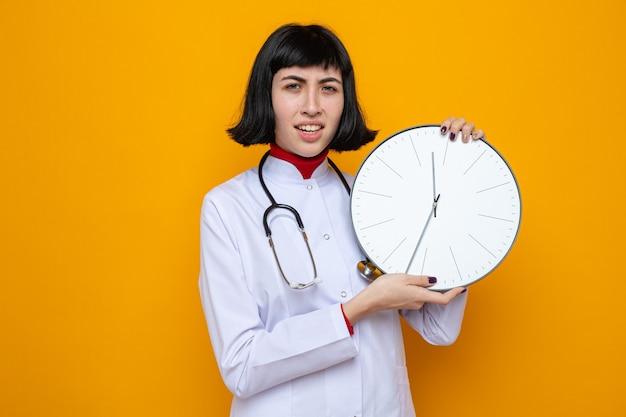 Unzufriedene junge hübsche kaukasische frau in arztuniform mit stethoskop, die uhr mit zwei händen hält