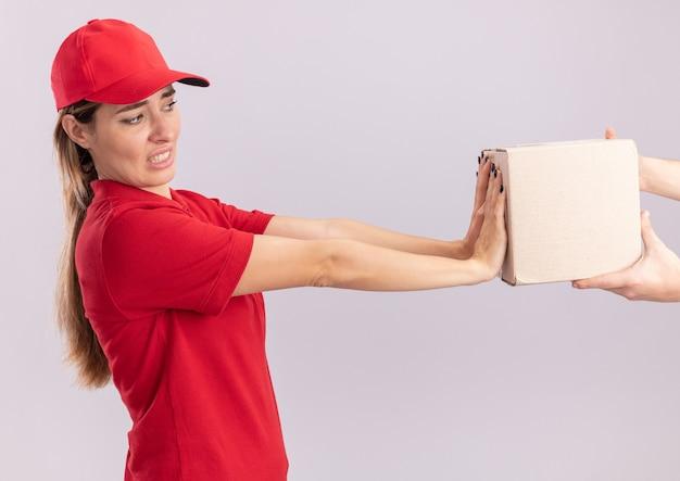 Unzufriedene junge hübsche lieferfrau in der uniform, die kartenbox jemand drückt, der isoliert auf weißer wand hält