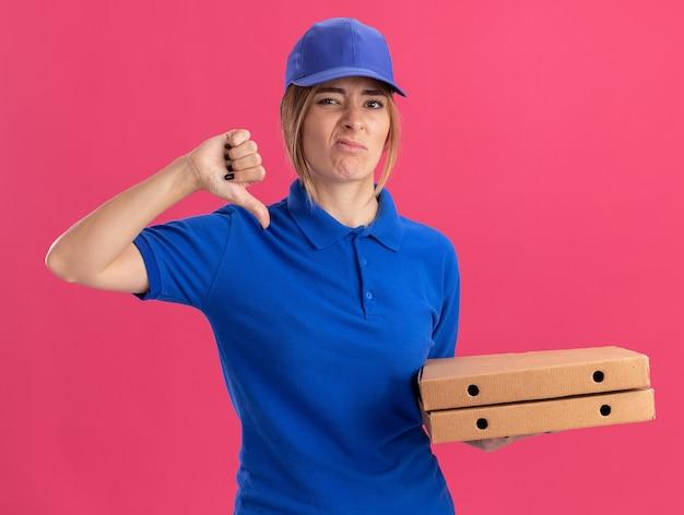 Unzufriedene junge hübsche lieferfrau in uniform daumen nach unten und hält pizzaschachteln isoliert auf rosa wand