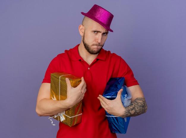Unzufriedene junge hübsche slawische partei kerl, der partyhut hält, der geschenkverpackungen betrachtet kamera lokalisiert auf lila hintergrund mit kopienraum