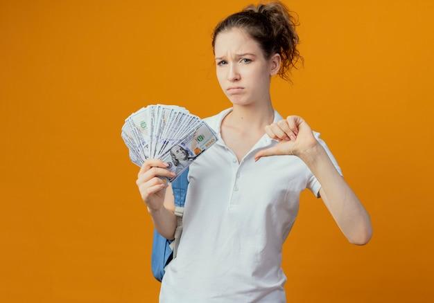 Unzufriedene junge hübsche studentin, die rückentasche hält, die geld hält und daumen unten auf orange hintergrund mit kopienraum zeigt