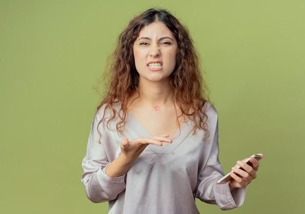 Unzufriedene junge hübsche weibliche büroangestellte halten und zeigt mit der hand am telefon lokalisiert auf olivgrüner wand