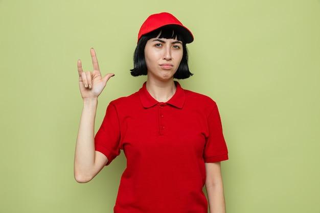 Unzufriedene junge kaukasische lieferfrau, die hörnerzeichen gestikuliert