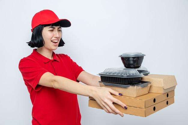 Unzufriedene junge kaukasische lieferfrau, die lebensmittelbehälter mit verpackungen auf pizzakartons hält und betrachtet