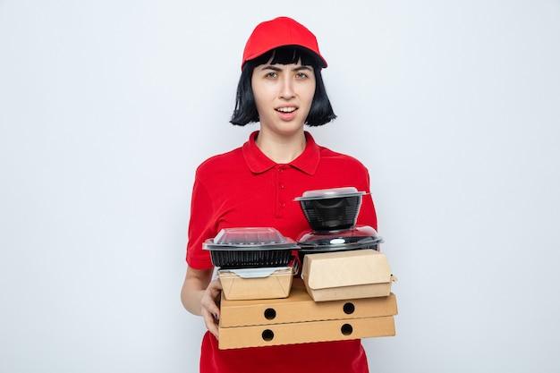 Unzufriedene junge kaukasische lieferfrau, die lebensmittelbehälter und verpackungen auf pizzakartons hält und schaut