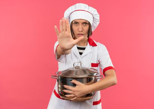 Unzufriedene junge köchin in der kochuniform, die topf hält und gestikuliert, stoppt an der kamera lokalisiert auf rosa hintergrund mit kopienraum