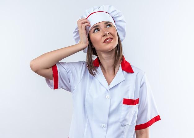 Unzufriedene junge köchin in kochuniform, die hand auf den kopf legt, isoliert auf weißem hintergrund
