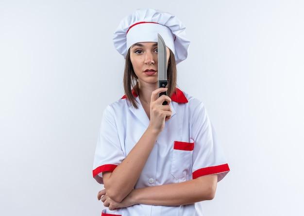 Unzufriedene junge köchin mit kochuniform bedeckte das auge mit dem messer isoliert auf weißem hintergrund