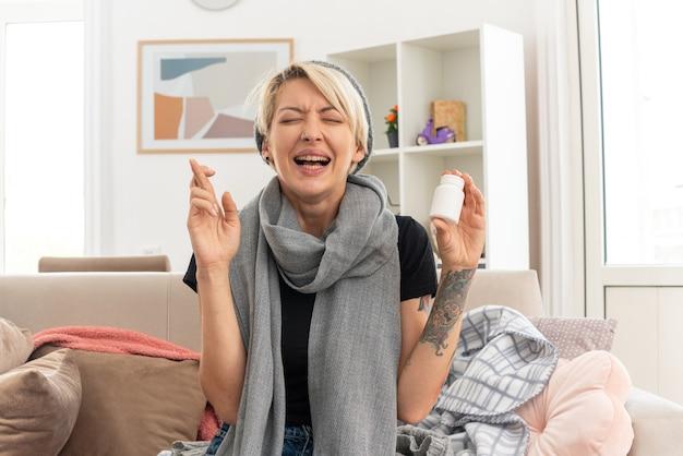 Unzufriedene junge kranke slawische frau mit schal um den hals, die eine wintermütze trägt, die eine medizinflasche hält und die finger mit geschlossenen augen im wohnzimmer auf der couch sitzt