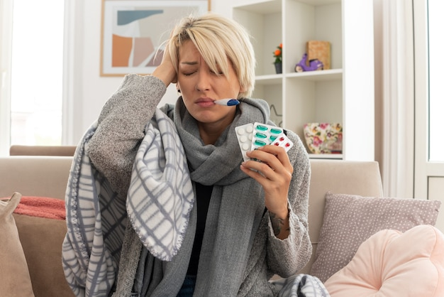 Unzufriedene junge kranke slawische frau mit schal um den hals, die in plaid gehüllt ist, ihre temperatur mit einem thermometer misst und medizinblisterpackungen hält, die auf der couch im wohnzimmer sitzen