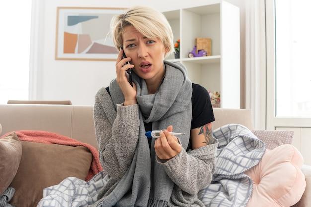 Unzufriedene junge kranke slawische frau mit schal um den hals, die thermometer hält und am telefon telefoniert, sitzt auf der couch im wohnzimmer