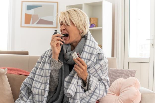 Unzufriedene junge kranke slawische frau mit schal um den hals, eingewickelt in karierte und beißende medizinblisterpackungen, die auf der couch im wohnzimmer sitzen