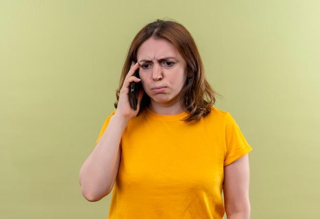 Unzufriedene junge lässige frau, die am telefon auf isolierter grüner wand mit kopienraum spricht