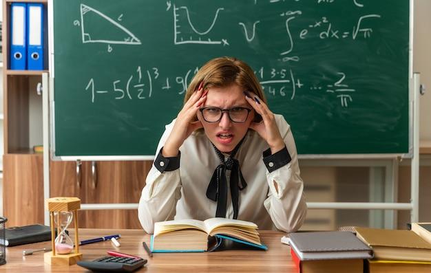 Unzufriedene junge lehrerin mit brille sitzt am tisch mit schulwerkzeugen, die die hände auf die tempel im klassenzimmer legen