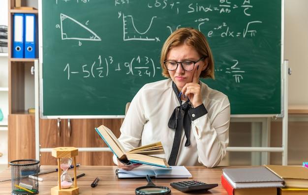 Unzufriedene junge lehrerin mit brille sitzt am tisch mit schulwerkzeugen, die ein buch im klassenzimmer halten und lesen
