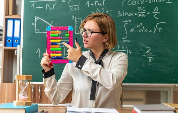 Unzufriedene junge lehrerin mit brille sitzt am tisch mit schulwerkzeugen und zeigt auf abakus im klassenzimmer