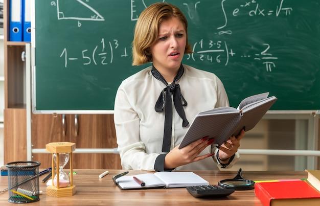 Unzufriedene junge lehrerin sitzt am tisch mit schulmaterial und liest buch im klassenzimmer