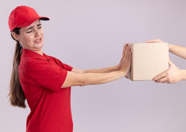 Unzufriedene junge lieferfrau in uniform und mütze, die in der profilansicht steht und dem kunden karton gibt, der die box anschaut, die eine ablehnungsgeste isoliert auf weißer wand macht