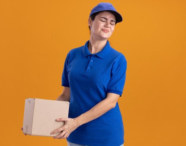 Unzufriedene junge lieferfrau in uniform und mütze