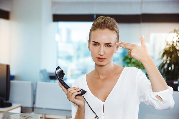 Unzufriedene junge schöne erfolgreiche geschäftsfrau, die telefon hält, über büro