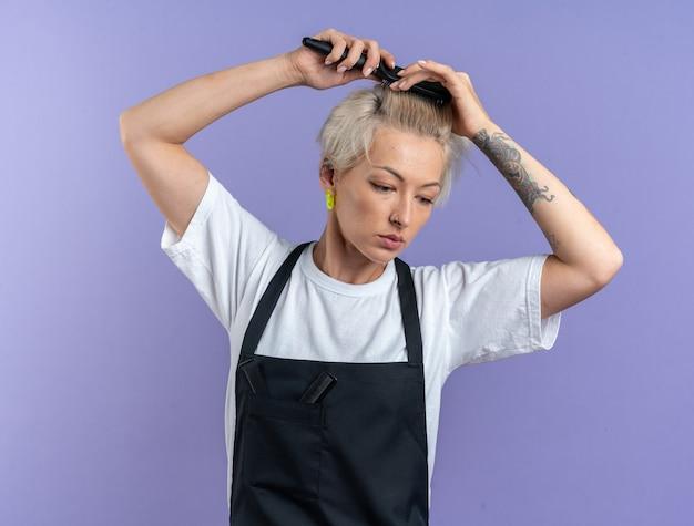 Unzufriedene junge schöne friseurin in uniform, die haare kämmt, isoliert auf blauem hintergrund