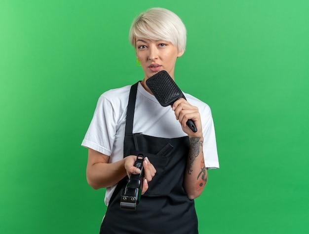 Unzufriedene junge schöne friseurin in uniform mit haarschneidemaschine mit kamm isoliert auf grünem hintergrund