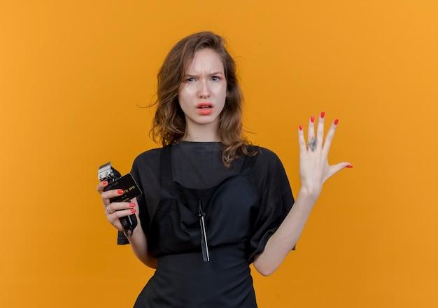 Unzufriedene junge slawische friseurin in uniform mit haarschneidemaschine und kreditkarte, die die hand in der luft hält