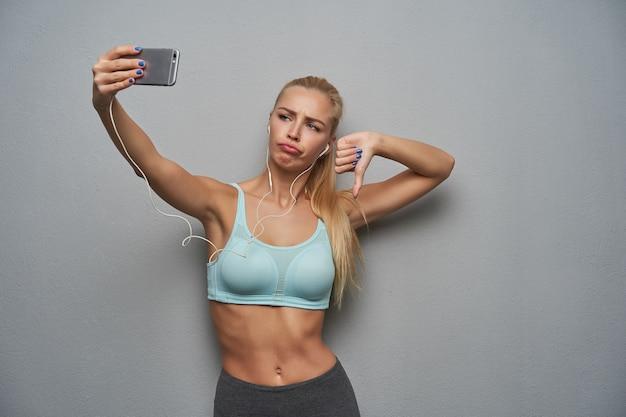 Unzufriedene junge sportliche blonde frau mit lässiger frisur, die foto von sich selbst macht und zur kamera mit schmollmund schaut, hand hebend, daumen unten zeigend, gegen grauen hintergrund stehend