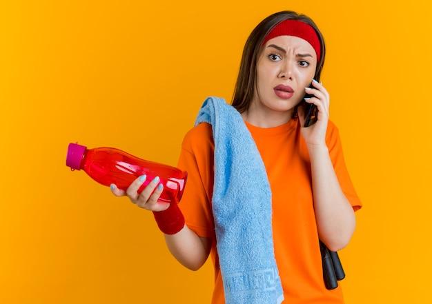 Unzufriedene junge sportliche frau, die stirnband und armbänder mit springseil und handtuch auf schultern hält wasserflasche hält und am telefon spricht, das seite schaut