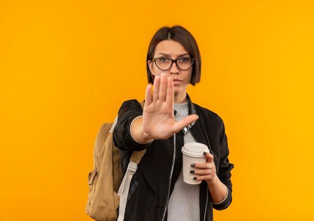 Unzufriedene junge studentin, die brille und rückentasche hält, die kaffeetasse gestikulierenden halt an der kamera lokalisiert auf orange hintergrund mit kopienraum hält