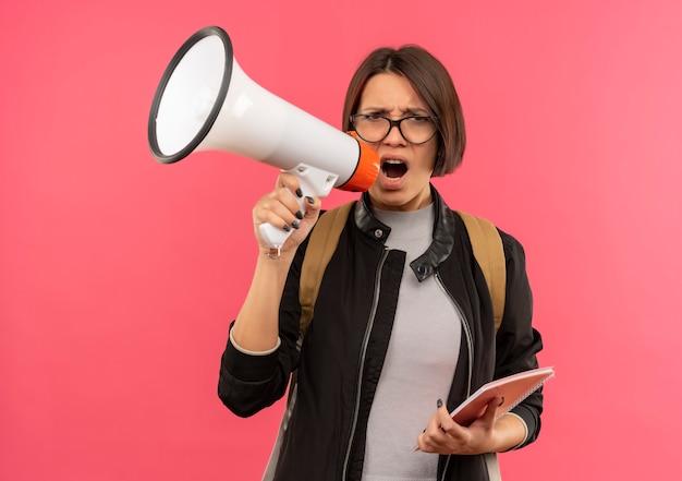 Unzufriedene junge studentin, die brille und rückentasche hält, die notizblock hält, der durch sprecher lokalisiert auf rosa hintergrund spricht
