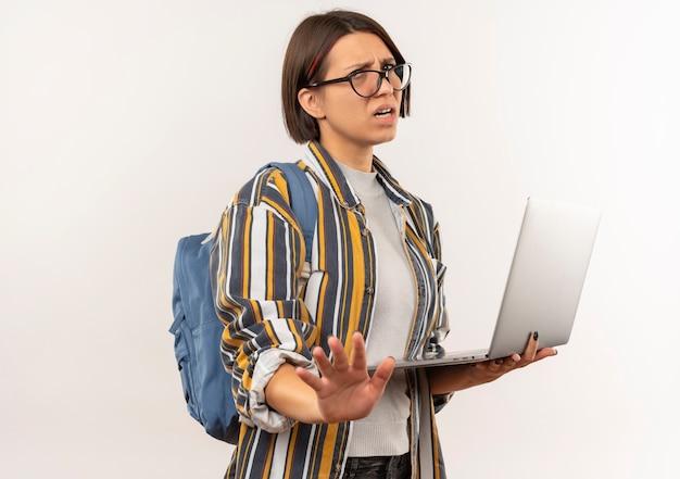 Unzufriedene junge studentin, die brille und rückentasche hält laptop hält, die keine geste lokalisiert auf weißem hintergrund mit kopienraum tut