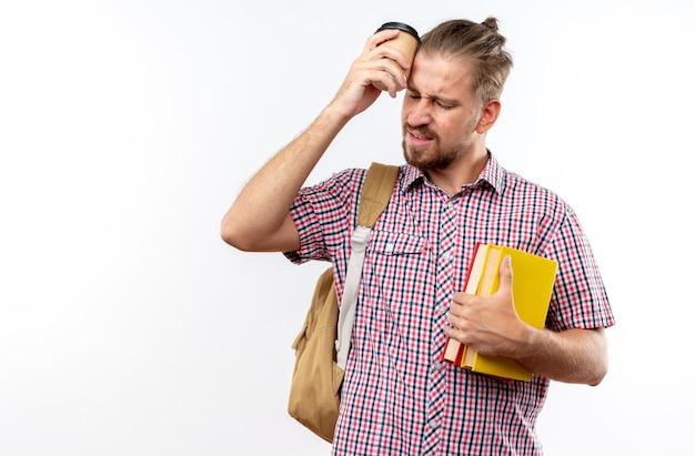 Unzufriedene junge studentin mit rucksack, die bücher hält und eine tasse kaffee auf die stirn stellt, isoliert auf weißer wand