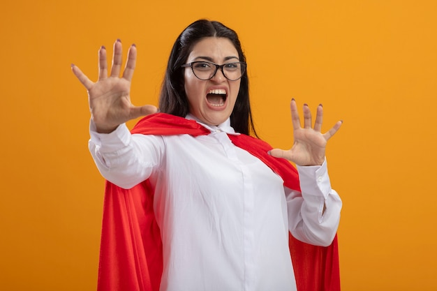 Unzufriedene junge superfrau, die eine brille trägt, die vorne schaut und keine geste tut, die auf orange wand isoliert wird