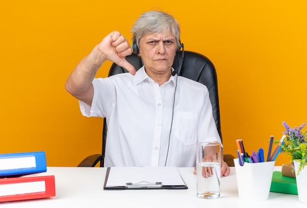 Unzufriedene kaukasische call-center-betreiberin auf kopfhörern, die am schreibtisch mit bürowerkzeugen sitzen, die isoliert auf orangefarbener wand herunterfallen?
