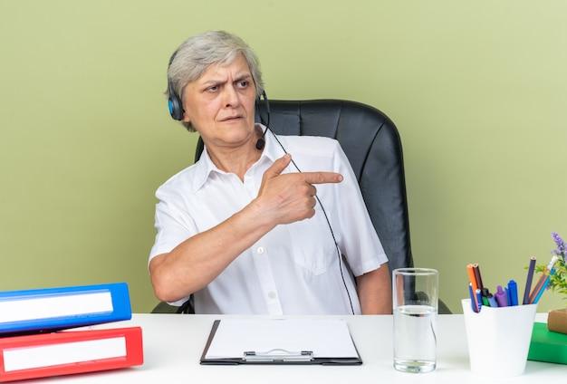 Unzufriedene kaukasische callcenter-betreiberin auf kopfhörern, die am schreibtisch mit bürowerkzeugen sitzen und auf die seite isoliert auf grüner wand zeigen und zeigen