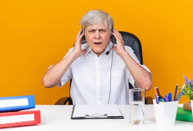 Unzufriedene kaukasische callcenter-betreiberin mit kopfhörern, die am schreibtisch mit bürowerkzeugen sitzen, die die hände auf die kopfhörer legen