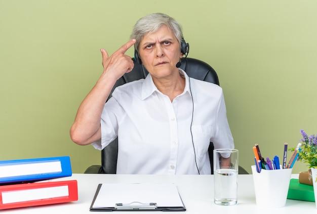 Unzufriedene kaukasische callcenter-betreiberin mit kopfhörern, die am schreibtisch sitzen und bürowerkzeuge auf ihr haar zeigen