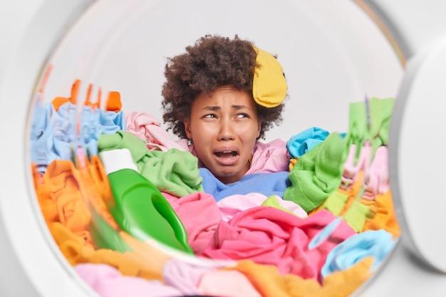 Unzufriedene lockige frau mit socke auf dem kopf weint vor verzweiflung, die von bunten wäscheposen durch waschmaschinentrommel bedeckt ist, fühlt sich müde von hausarbeit