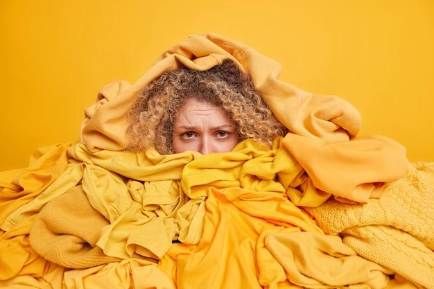 Unzufriedene, lockige junge frau, die in einem haufen entfalteter kleidung begraben ist, die zum recycling oder zur spende gesammelt wurde, hat einen frustrierten blick, der über gelb isoliert ist