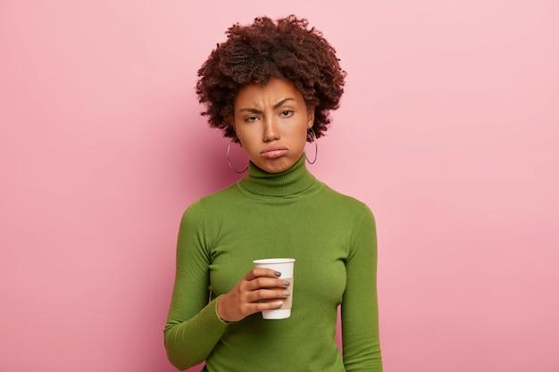 Unzufriedene müde afroamerikanerin hält kaffee zum mitnehmen, versucht sich nach harter arbeit zu erfrischen, trägt einen grünen polohalspullover, seufzt vor müdigkeit, fühlt sich überarbeitet