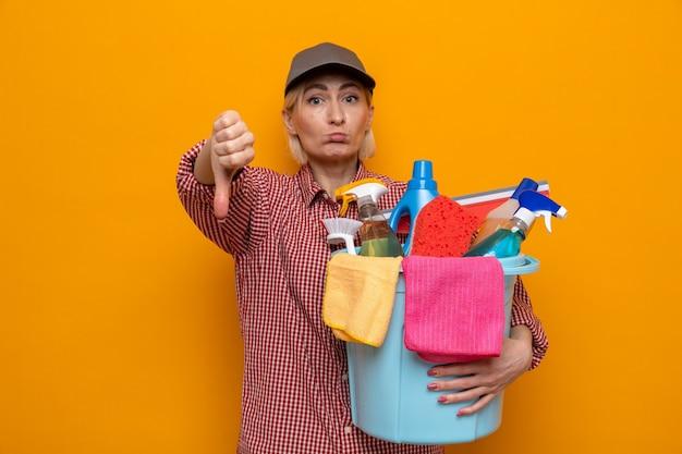 Unzufriedene putzfrau in kariertem hemd und mütze mit eimer mit reinigungswerkzeugen, die daumen nach unten zeigen