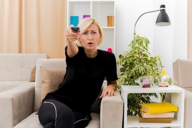 Unzufriedene schöne blonde russische frau sitzt auf sessel, der fernsehfernbedienung hält und kamera im wohnzimmer betrachtet
