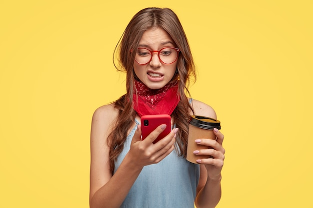 Unzufriedene schöne frau schaut mit ekel und abneigung auf handy, bearbeitet foto in spezieller app, trinkt kaffee zum mitnehmen, posiert über gelber wand, fühlt sich nicht mögen, verbunden mit highspeed-internet
