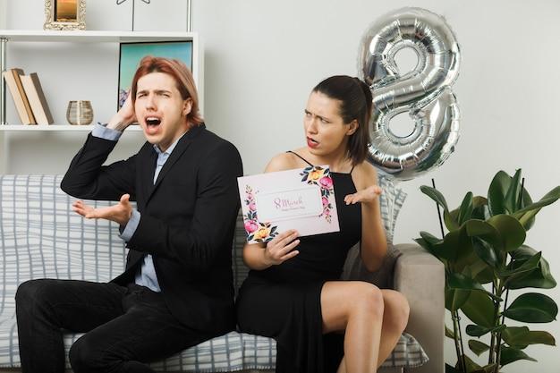 Unzufriedene, sich ausbreitende hände junges paar am glücklichen frauentag, der eine grußkarte auf dem sofa im wohnzimmer hält