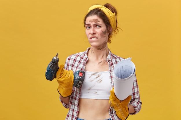 Unzufriedene technikerin mit schmutzigem gesicht und kleidung, die sich auf die lippe beißt, und stirnrunzelndem gesicht, das das bauinstrument und die blaupause hält und nicht arbeiten will