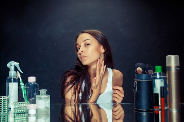 Unzufriedene unglückliche junge frau, die ihr selbst im spiegel auf schwarzem studiohintergrund betrachtet. problem haut und akne konzept. morgen, make-up und menschliche emotionen konzepte. kaukasisches modell im studio